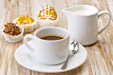 coffee, sugar, milk and cakes on wooden board textured photo
