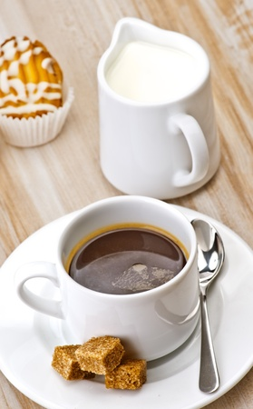 coffee, sugar, milk and cakes on wooden board textured