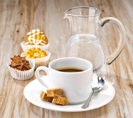 coffee, sugar, water and cakes on wooden board textured Stock Photo
