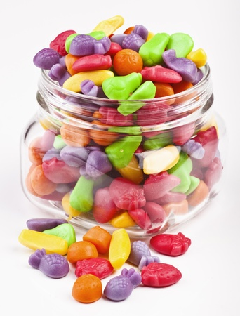 colored jelly beans in glass jar isolated on white photo