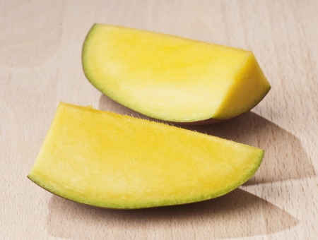 sectioned: Mango sectioned on a wooden base Stock Photo
