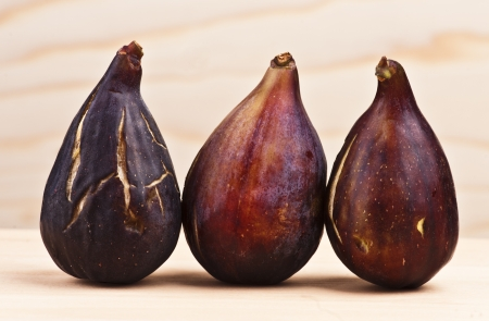 group of figs on wooden base and wooden background photo