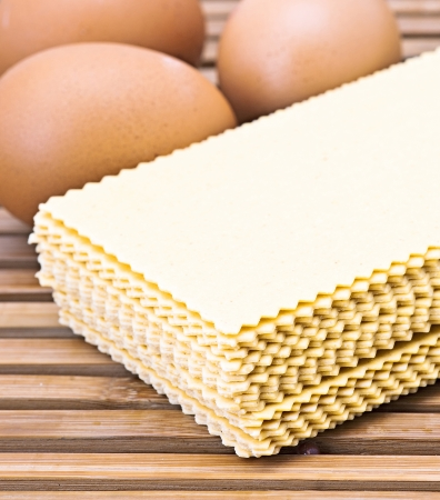 raw lasagna pasta with eggs, ready to be cooked on wooden slats base photo