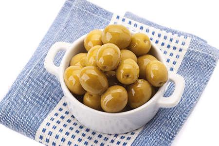 green olives in white porcelain bowl on serviette flat