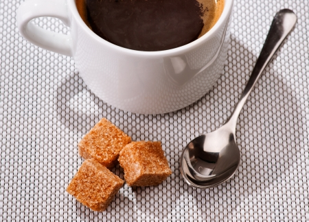 black sugar spoon and coffee cup on braided rug photo