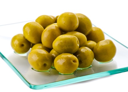 pitted: green olives on a plate of glass, isolated on white