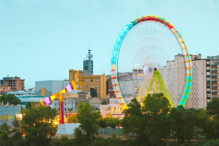 Fair Ferris wheel adorned with lights spinning at dusk photo
