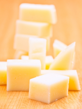 chees: cheddar cheese cut into cubes, on wooden base Stock Photo