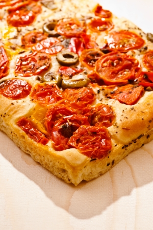 focaccia with tomatoes, olives, artichokes and vegetables, isolated on white base photo