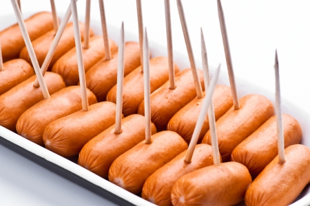 cocktail sausages; punctured tray with chopsticks Stock Photo
