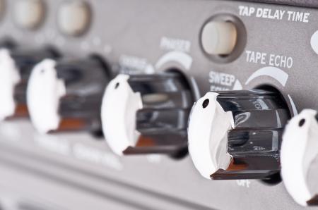 controls of a guitar amplifier, making macro photo