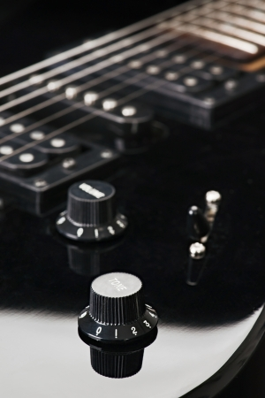 controls and cords, of a black electric guitar Stock Photo