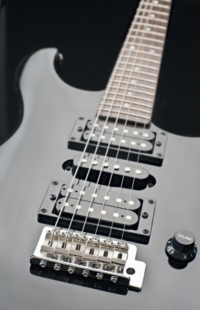detail of a black electric guitar photo