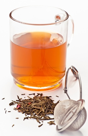 Cup with tea, dried tea before and metal handle for infusions
