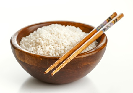 Wooden bowl with rice and Chinese chopsticks