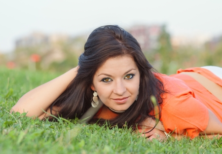 young girl lying in grass resting a cloudy day Stock Photo