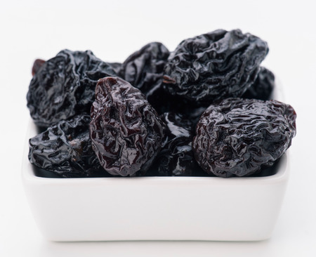 group of prunes in small porcelain tray photo