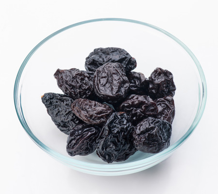 lot of prunes in transparent glass bowl photo