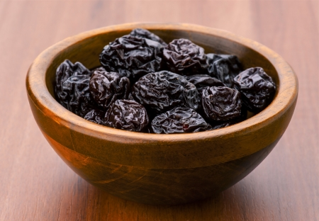 prunes group in wooden bowl photo