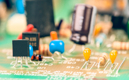 transistor: transistor surrounded by other components mounted on motherboard Stock Photo