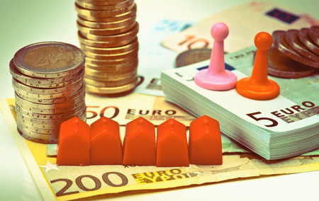 housing crisis: coins, bills, buildings and people Stock Photo