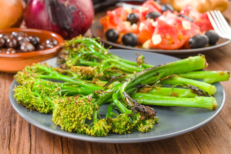 dish with tender shoots of broccoli and grilled tomato salad Stock Photo
