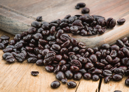 plenty of roasted coffee beans on wooden board Stock Photo
