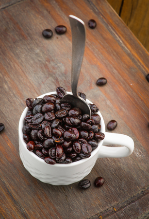 cup filled with roasted coffee beans on wooden board Stock Photo