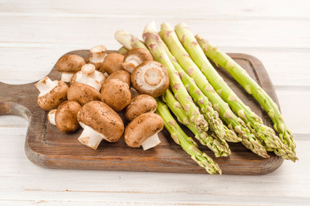 green asparagus and raw brown mushrooms on wooden board Stock Photo
