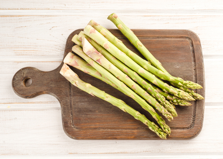 green asparagus on white wood listed