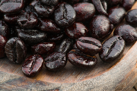 macro shot of roasted coffee beans on wooden board