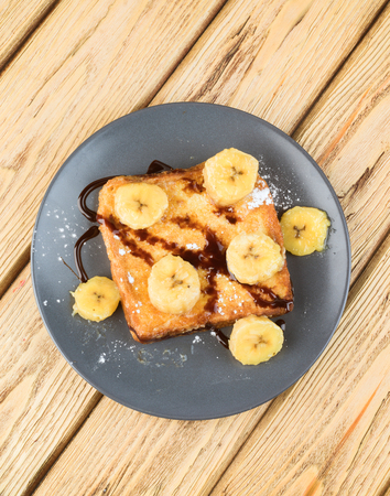 zenith: French toast with banana and chocolate on wood; takes zenith