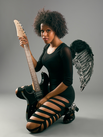 beautiful black girl with angel wings and electric guitar, studio shooting