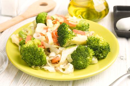 naturist: steamed vegetables in modern plate, on wooden board