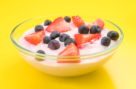 thinness: bowl of strawberry yogurt with sliced strawberries and blueberries, isolated on yellow