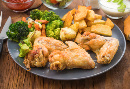 fried chicken wings: fried chicken wings with salad and sauces Stock Photo