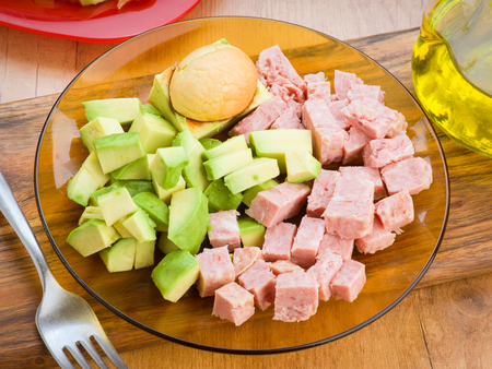 diced: chopped avocado and diced cooked ham on plate on wooden base Stock Photo