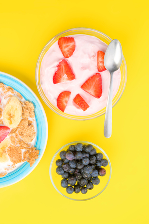 thinness: akes zenithal of a bowl of strawberry yogurt with sliced strawberries, isolated on yellow