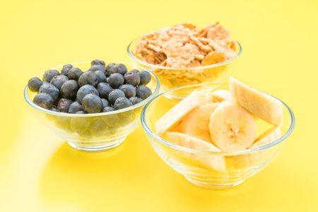 thinness: bowls of cereal, banana and blueberries, on yellow background Stock Photo