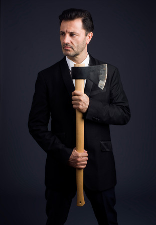 pitman: dressed man in studio shows an ax