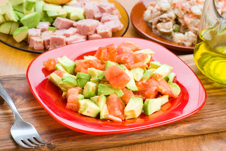 diced: chopped avocado and diced tomato on plate on wooden base