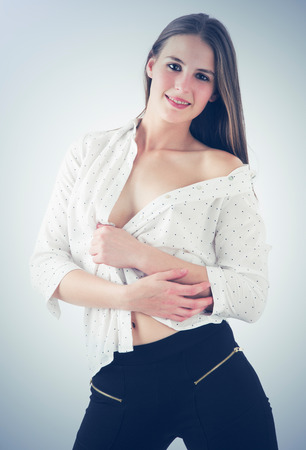 women undressing: girl with unbuttoned shirt posing in studio Stock Photo