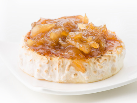 caramelized: piece of goat cheese with caramelized onions over white background