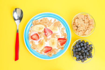 thinness: takes zenithal of strawberries bowl of cereal with milk and sliced banana on white background