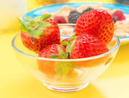 thinness: approximation of whole strawberries in bowl with other berries, yellow background