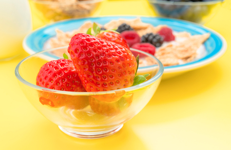 approximation: approximation of whole strawberries in bowl with other berries, yellow background