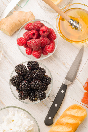 breackfast: Vertical making Blackberries and blueberries at the breakfast table Stock Photo