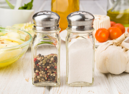 pepperbox: salt and pepper shakers in front of a salad on wood