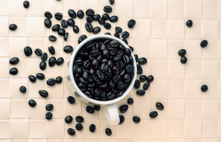 black beans: cup full of coffee beans