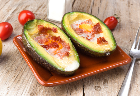 obscurity: stew baked avocado with egg on old wooden table